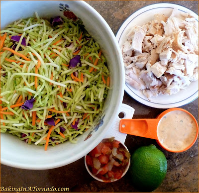 Spicy Broccoli Slaw and Chicken Salad, for lunch or for dinner on a hot summer night. Mix just a few ingredients together, refrigerate, let everyone choose their favorite toppings when you're ready to serve. | Recipe developed by www.BakingInATornado.com | #recipe #salad #chicken