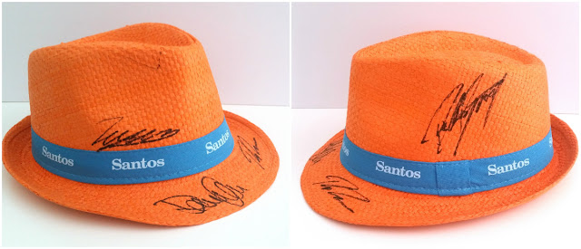 "A collage of two photos of the same hat showing the autographs written on both sides of an orange hat with a blue band. The blue band has the sponsor's name printed in white text ""Santos"". The signatures are written in black texta."