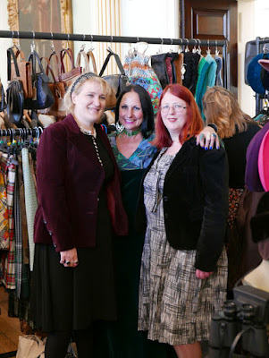Three women in front of a vintage clothing stall