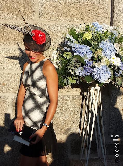 Invitada boda con vestido estampado geométrico en blanco y negro, tocado tipo plato en negro y flor rojo con plumas de faisán. Fondo con gran ramo de hortensias.
