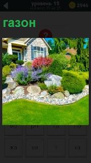 Около дома разбит красивый газон с цветами и кустами, огражденный декоративным камнем