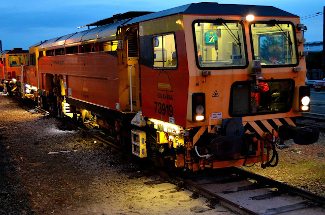 Night photo of Colas Rail track machine 73919 on sidings at Ely railway station