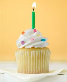 Fotografia colorida, com fundo amarelo, de um cupcake coberto com suspiro branquinho, enfeitado com confeitos coloridos e uma velinha verde acesa, sobre toalha branca (crédito Ver Com Palavras)