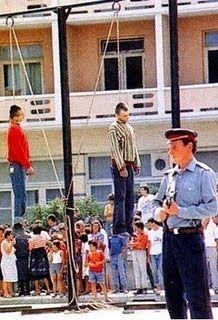 Policía con arma y dos hombres colgados (plaza pública en Irán)