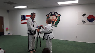 Taekwondo martial art lady recieving her new black belt
