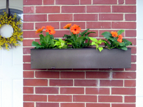 We now have an awesome upcycled floating planter box on our brick wall!