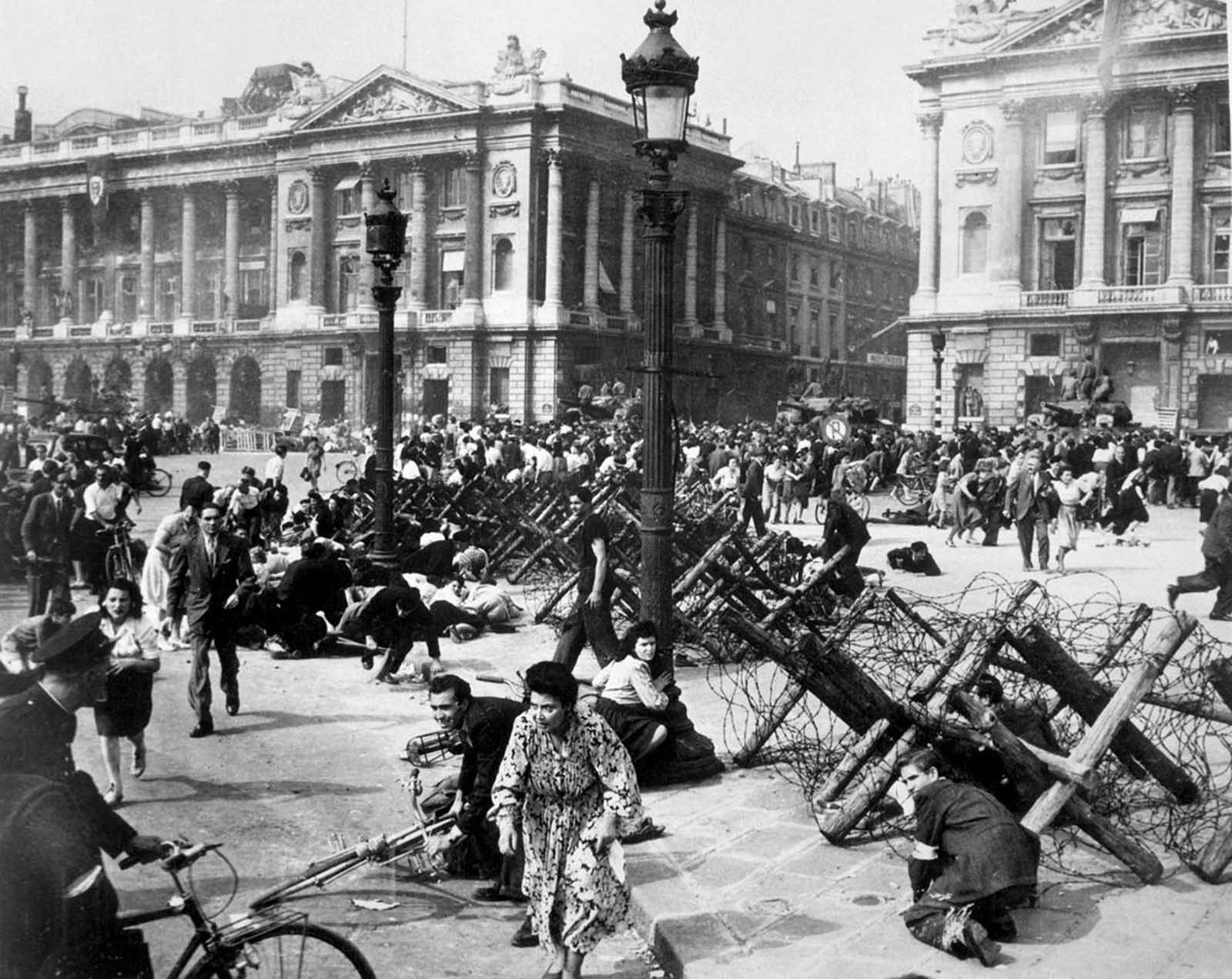Crowds of Parisians celebrating the entry of Allied troops into Paris scatter for cover as a sniper fires from a building on the place De La Concorde. Although the Germans surrendered the city, small bands of snipers still remained. August 26, 1944.