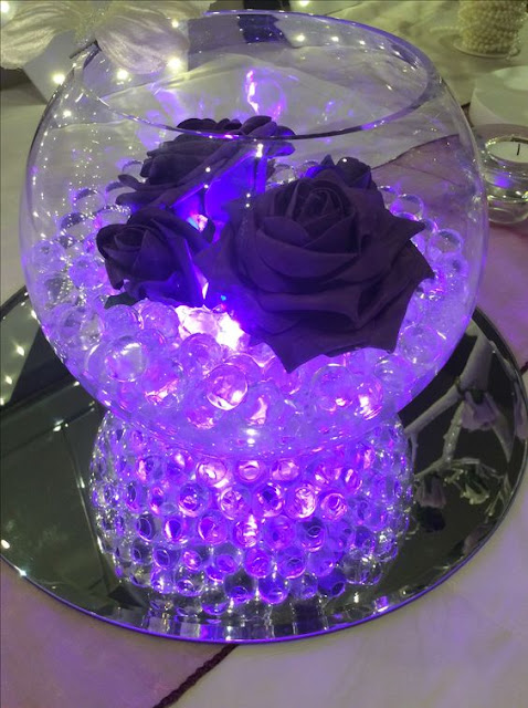 Led Lighting set up with roses for wedding fish bowl masterpiece design with purple aqua crystals