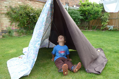 Child in a tent made from garden canes