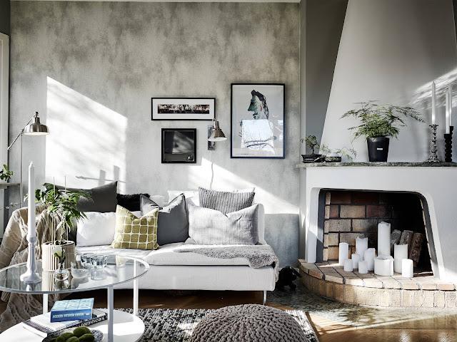 biały kominek, biała sofa, szara ściana w salonie