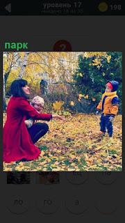 Осенью в парке гуляет мама с ребенком и собирают пожелтевшие листья