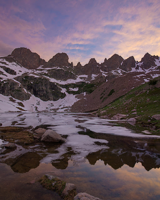 Upper willow lake in the Eagles Nest Wilderness at sunset with the Zodiac Ridge reflected in the half frozen waters
