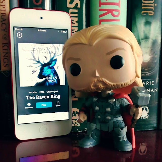 A very angry, large-headed Funko Pop of Marvel's Thor stands beside a white iPod with the cover of The Raven King on it. The cover features the silhouette of an enormous elk with swirling blue light in it.