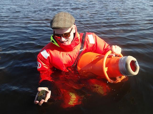 Pelastautumispukuinen henkilö vesikiikarin kanssa seisoo vedessä, kivi kädessä