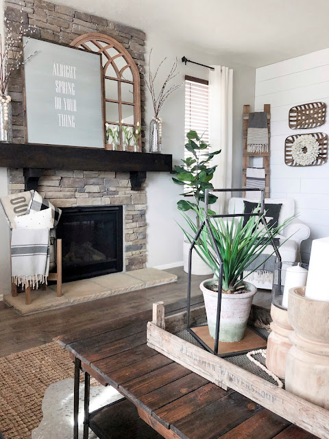 "Spring farmhouse styled fireplace, arched mirror, large sign that says ""Alright Spring do your thing"" white tulips, glass vases"
