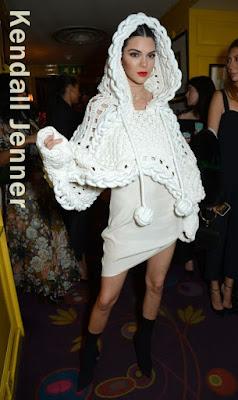 この日のケンダル・ジェンナー(Kendall Jenner)は、光沢のあるキャミソールワンピースにバーバリー(Burberry)のフード付きケープを纏い、ヒールが特徴的なニット素材のブーツでカジュアルさも出しつつ、エレガントなスタイルを披露。また、歯にグリルをつけてオシャレ度Up。