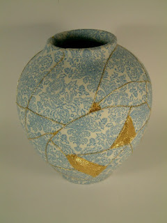A broken vase with its cracks repaired with gold