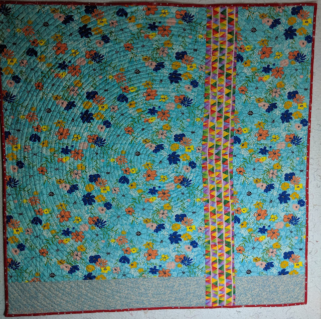 The back is composed of a large floral on light blue extended with a quiet blue print. A remnant of the wide border from the front cuts across these fabrics dividing the sides about a third of the way across.