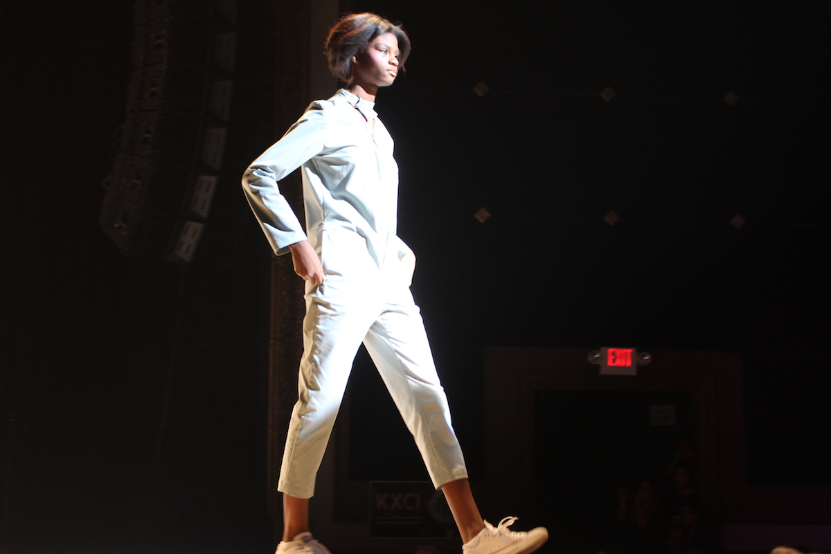 This is a photo of a model wearing a white jumpsuit as she walks down the runway.