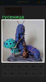 Небольшая статуэтка с гусеницей синего цвета и грибы зеленого цвет