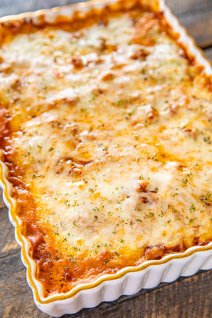 Million Dollar Ravioli Casserole - seriously delicious! Meat sauce, frozen ravioli, and 4 cheeses! The BEST pasta casserole EVER!!! Can make ahead and refrigerate or freeze for later. Frozen cheese ravioli, cream cheese, sour cream, cottage cheese, Italian sausage, spaghetti sauce, parmesan cheese and mozzarella cheese. Serve with a simple salad and garlic bread. Great for dinner parties and potlucks! Everyone loves this easy casserole! I never have any leftovers!! #casserole #pasta #freezermeal