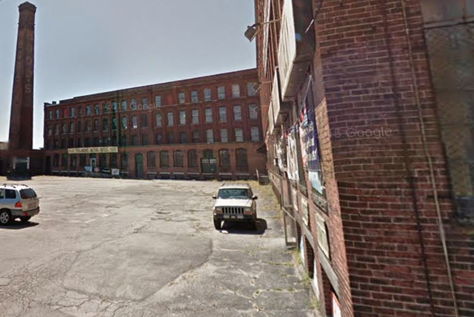 Google Street View shows parking lot, chimney and red brick facade of C.I. Hood's Laboratory (factory)