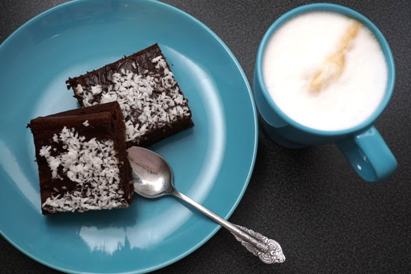 brownie z fasoli z daktylami i syropem z agawy, z polewą czekoladową i wiórkami kokosowymi na niebieskim talerzu