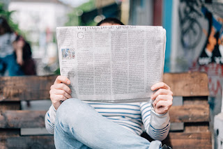 Person sitting on a park bench reading a newspaper