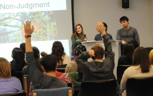 Three Spanish beginner students deliver a teaching session, standing at the front of a classroom. Various members of the audience have their hands up in response to a question.