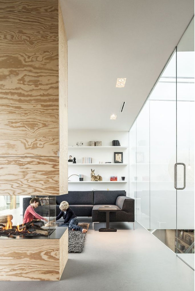 Wooden fireplace in living room of Modern Villa V by Paul de Ruiter Architects