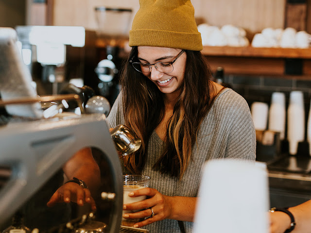 young, smiling barista preparing a coffee