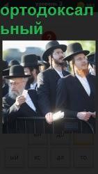 несколько мужчин ортодоксальных стоят в котелках и костюмах