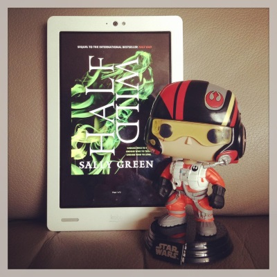A large-headed Funko Pop bobblehead of Poe Dameron stands to the viewer's right of a white Kobo with Half Wild's cover on its screen. The cover features acid green smoke that swirls into the outline of a howling wolf against a black background.