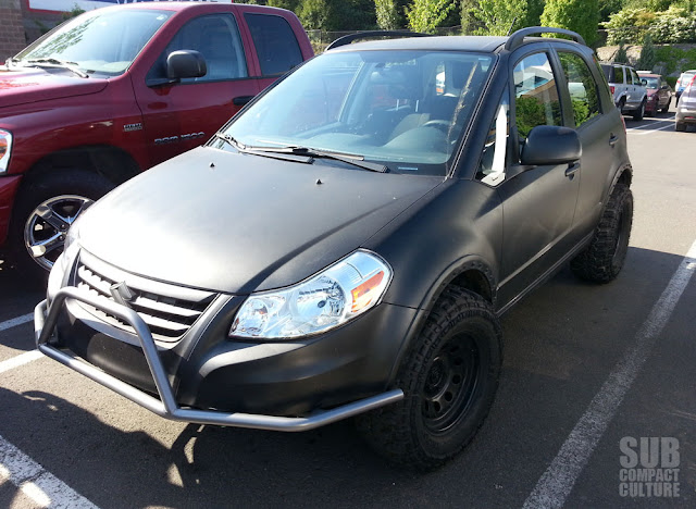Flat black Suzuki SX4 on off-road wheels/tires with custom off-road bumper