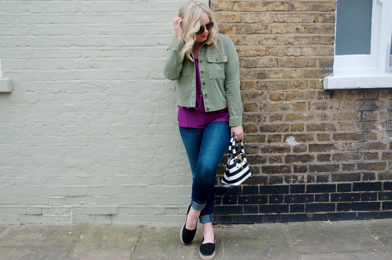 purple top, green jacket, necklace, jeans, striped bag, black shoes and sunglasses