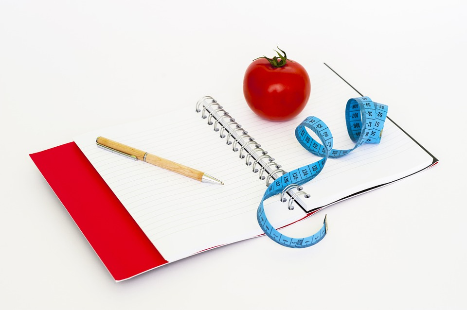 photo of notebook, apple, tape measure, pen