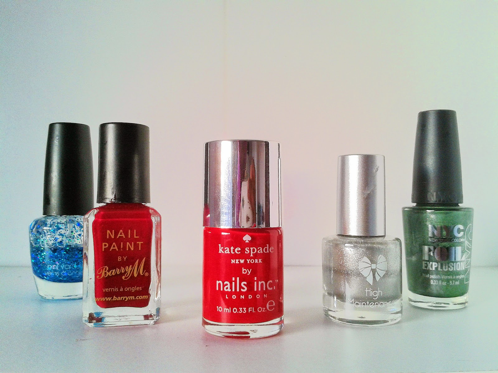 A shot of five nail polishes. From left to right: glittery blue, dark berry, apple red, silver and emerald green