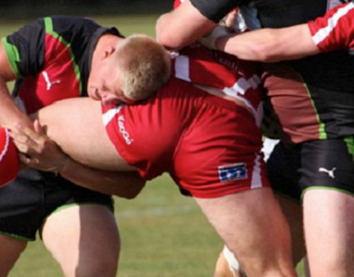 Rugby players grab and hold strong legs and butt in a scrimmage