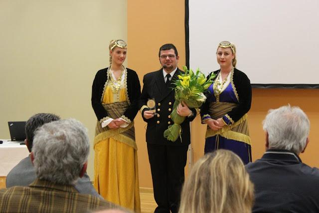 Ο Υποπλοίαρχος του Πολεμικού Ναυτικού με την τιμητική πλακέτα, που του απένειμε ο πρόεδρος της Ένωσης Ποντίων Σουρμένων Γιώργος Σαραφίδης, πλαισιωμένος από κορίτσια του χορευτικού