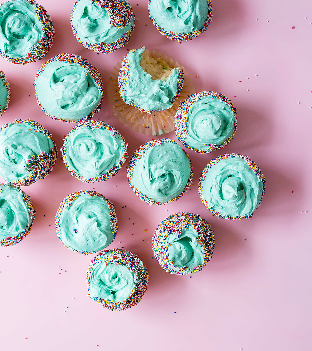 Some thoughts on my 25th birthday and turning a quarter century. teal icing and rainbow sprinkle cupcakes flatlay