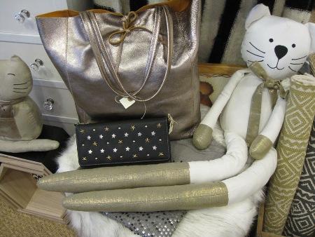 Gato blanco, bolso dorado y cartera de mano negra y dorada.