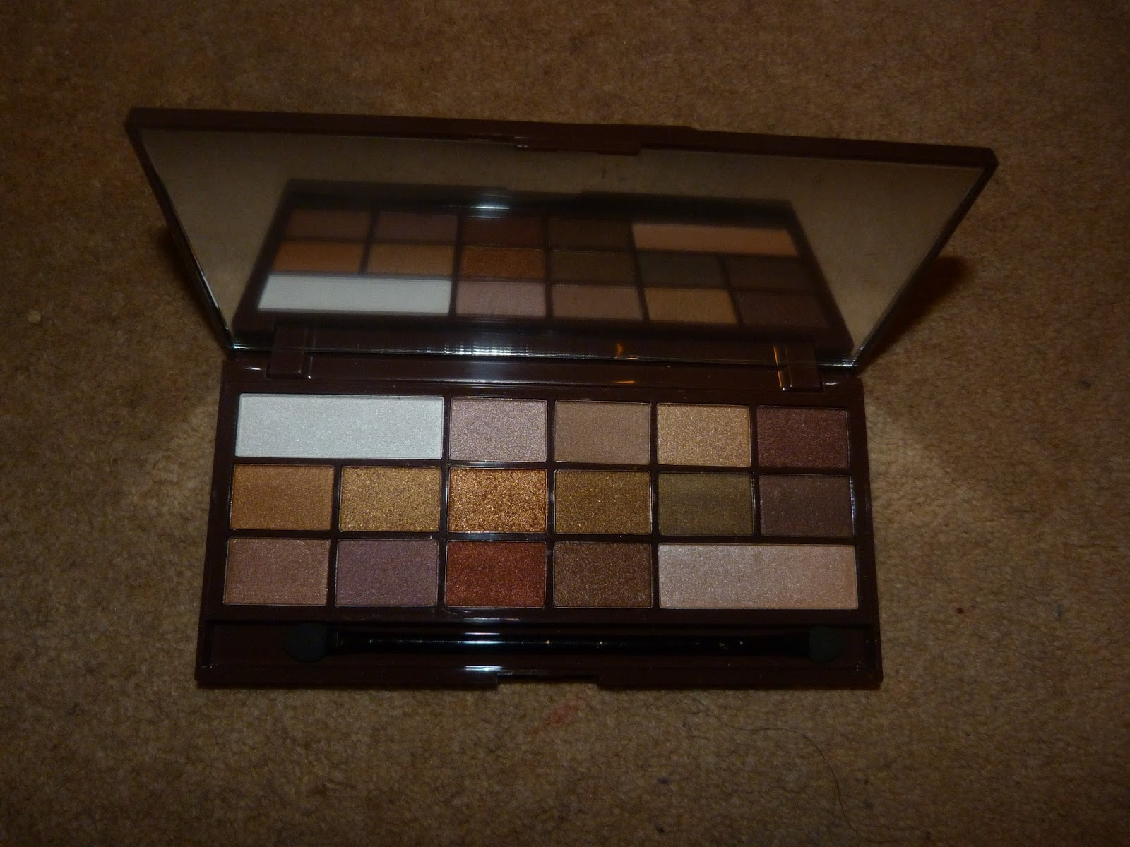This palette has 16 shimmery eyeshadows in it in gold and brown shades it also has two paler colors in it a shimmery white and a shimmery nude color