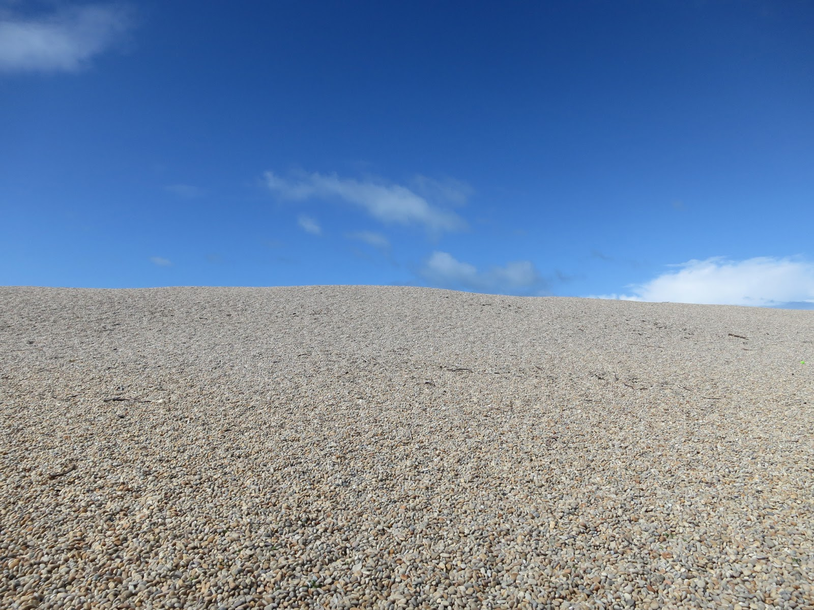 Towards the top of Chesil Beach. Pebbles with blue sky.
