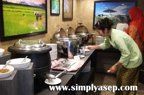SIAP : Salah seorang kru Resoran Dangau sedang memanaskan menu yang akan disajikan kepada para tamu hari itu.  Foto Asep Haryono