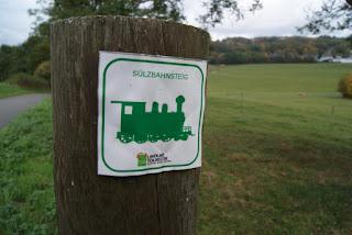 """Ein Holzpfosten, an dem ein weißes Blechschild geschraubt ist. Auf dem Blechschild sieht man eine grüne Dampflok, darüber den Schriftzug """"Sülzbahnsteig"""". Im Hintergrund ist eine Weide sowie eine Straße zu erkennen."""