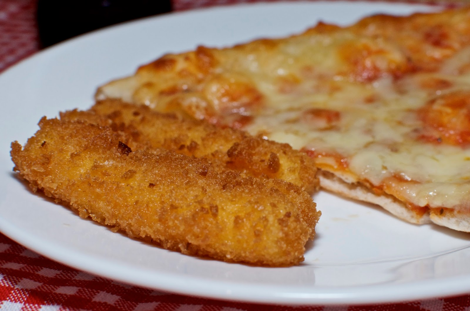 Mozzarella cheese sticks and pizza on white plate