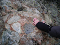 Head-sized rocks of various shades embedded in a reddish-brown cement which is made of volcanic ash. A hand is on the rock for scale.