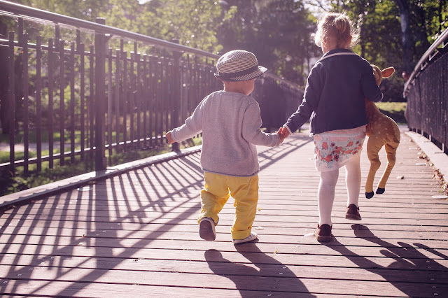 2 children running across a wooden bridge.