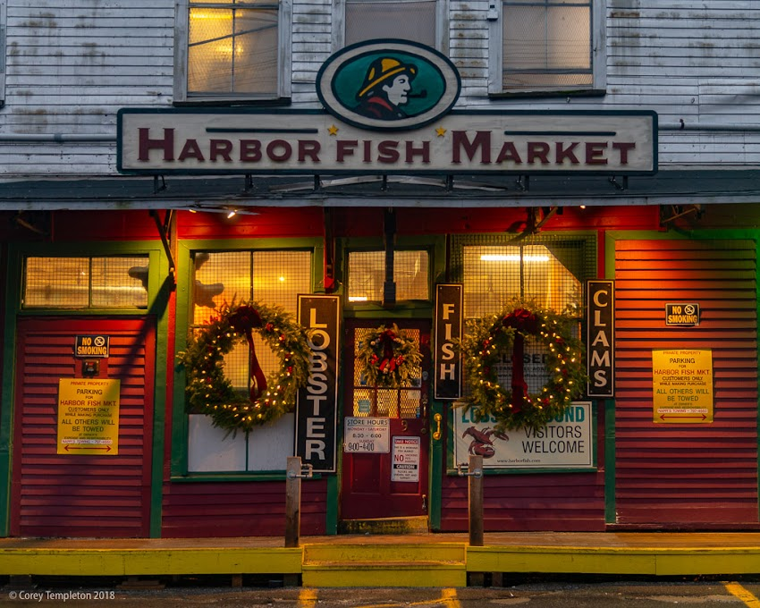 Portland, Maine USA December 2018 photo by Corey Templeton. Wreaths across the entrance of Harbor Fish Market on a recent morning. Custom House Wharf in the Old Port.