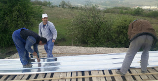 Three men fixing a metal sheet to the roof